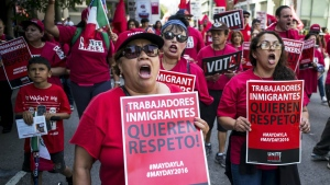 """Hundreds of May Day marchers chanting slogans and carrying signs - these say 'Immigrant Workers Want Respect""""- and at least one Donald Trump pinata, take to the streets of Los Angeles, calling for immigrant and worker rights and decrying what they see as hateful presidential campaign rhetoric, Sunday, May 1, 2016. (David Crane / Los Angeles Daily News)"""