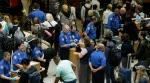 TSA agents check passenger boarding passes and identification at a security screening checkpoint, Thursday, May 19, 2016, at Seattle-Tacoma International Airport in Seattle. (AP Photo/Ted S. Warren)