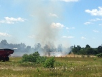 Smoke and flames can be seen coming from a field in Essa Township, Ont. as firefighters battle a blaze on Friday, July 22, 2016. (Don Wright/ CTV Barrie)