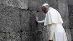 Pope Francis prays in front of the death wall at the former Nazi concentration camp of Auschwitz in Oswiecim, Poland, Friday, July 29, 2016. Pope Francis paid a somber visit to the Nazi German death camp of Auschwitz-Birkenau Friday, becoming the third consecutive pontiff to make the pilgrimage to the place where Adolf Hitler's forces killed more than 1 million people, most of them Jews. s. (L'Osservatore Romano /Pool Photo via AP)