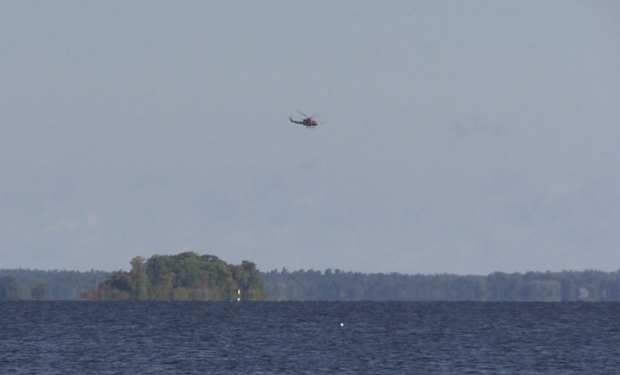 A helicopter flies above Georgian Bay, near Midland, Ont. as part of a search and rescue operation on Tuesday, Aug. 23, 2016. (Roger Kleiné CTV Barrie)