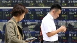 People look at their mobile phone at an electronic stock board of a securities firm in Tokyo, Friday, Oct. 21, 2016. (AP / Koji Sasahara)