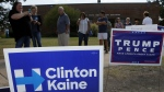Early voters stand by campaign signage as they wait in line at a voting location in Dallas on Thursday, Oct. 27, 2016. (AP / Tony Gutierrez)