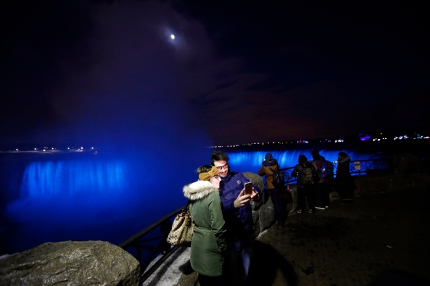 In this Saturday, Dec. 10, 2016 photo, people take a selfie near the Niagara Falls illuminated by new LED lights. (Julio Cortez / THE ASSOCIATED PRESS)